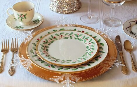 Christmas Dinner planning tips - table set for formal meal with Christmas patterned dinnerware